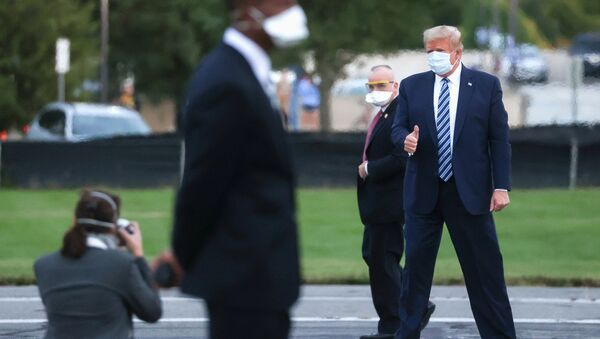 U.S. President Donald Trump gives a thumbs up to a White House staff photographer as he stands on the helipad of Walter Reed National Military Medical Center while preparing to board the Marine One helicopter to fly back to the White House in Washington after a fourth day of treatment for the coronavirus disease (COVID-19) at the hospital in Bethesda, Maryland, U.S., October 5, 2020. REUTERS/Jonathan Ernst - Sputnik International
