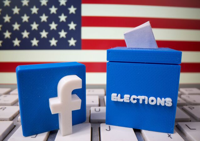 A 3D-printed elections box and Facebook logo are placed on a keyboard in front of U.S. flag in this illustration