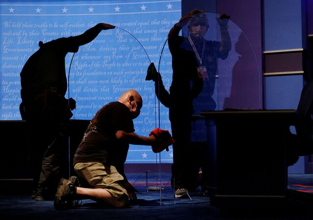 Commission on Presidential Debates staff clean the freshly installed protective plexiglass panels put in place as a coronavirus disease precaution between the candidates' seats for the 2020 vice presidential debate between Vice President Mike Pence and Democratic vice presidential nominee and U.S. Senator Kamala Harris on the campus of the University of Utah in Salt Lake City, Utah, U.S., October 6, 2020