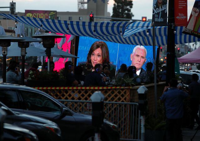 People watch the debate between U.S. Vice President Mike Pence and Democratic vice-presidential nominee Kamala Harris outside a tavern in San Diego, California, U.S., October, 7, 2020.