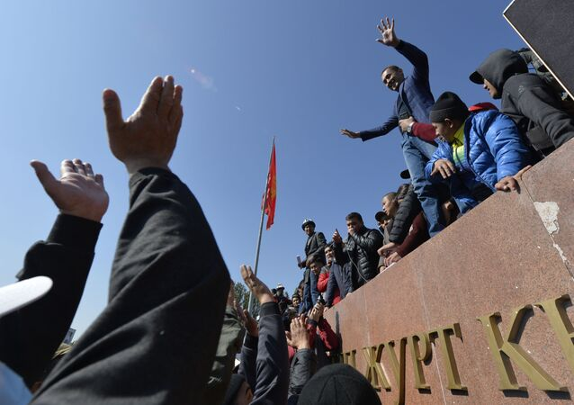 People protest during a rally on the central square in Bishkek, Kyrgyzstan, Wednesday, Oct. 7, 2020. Officials in Kyrgyzstan have nullified the results of a weekend parliamentary election after mass protests erupted in the capital of Bishkek and other cities, with opposition supporters seizing government buildings and demanding a new vote.