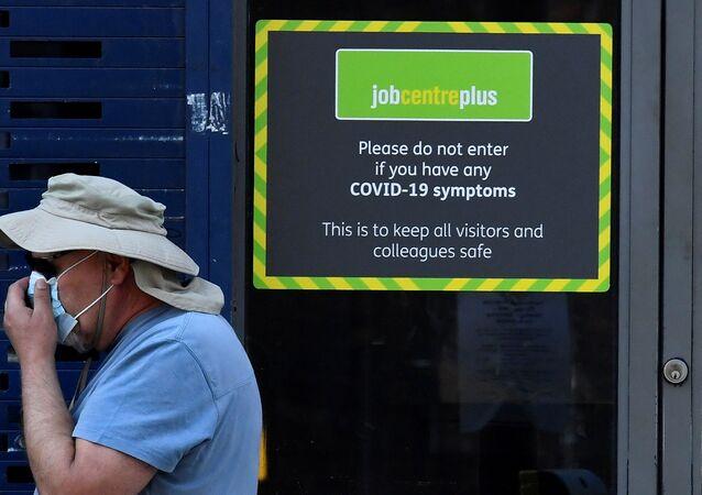 A person wearing a protective face mask walks past a Job Centre Plus office, amidst the outbreak of the coronavirus disease (COVID-19) in London, Britain, August 11, 2020.