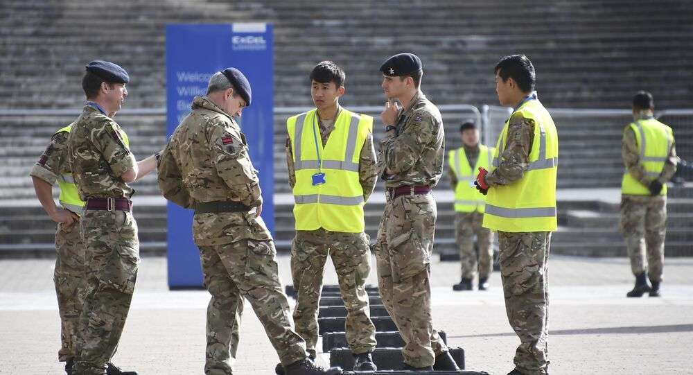 British Army soldiers get instructions outside the ExCel center which is being turned in to a 4000 bed temporary hospital for coronavirus patients in London, Tuesday, March 31, 2020.
