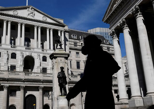A person wearing a mask walks past the Bank of England in London, Britain, March 23, 2020