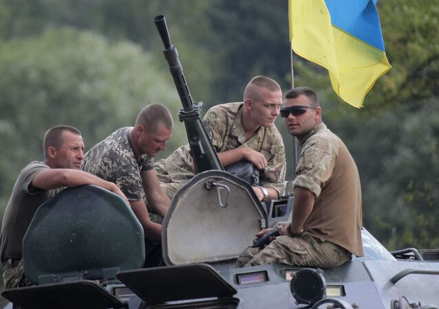 Ukrainian soldiers atop an APC watch training exercises under the supervision of British instructors on the military base outside Zhitomir, Ukraine, Tuesday, Aug. 11, 2015