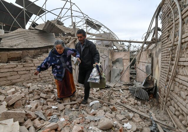 A man helps an elderly woman to walk out of a damaged house carrying her belongings following the recent shelling by Armenian forces, in Ganja, Azerbaijan.