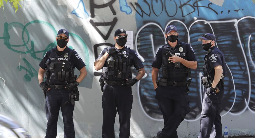 Seattle Police officers stand in front of a wall of graffiti as they wait across the street from a rally in support of police and other law enforcement officers, Wednesday, July 15, 2020, in front of City Hall in Seattle