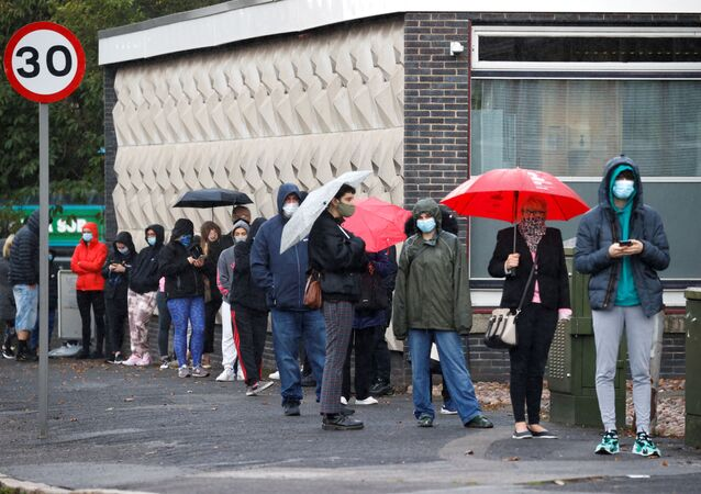 People stand in a queue to get tested for COVID-19 at a walk-through centre amid the coronavirus disease (COVID-19) outbreak in Liverpool Britain, October 6, 2020.