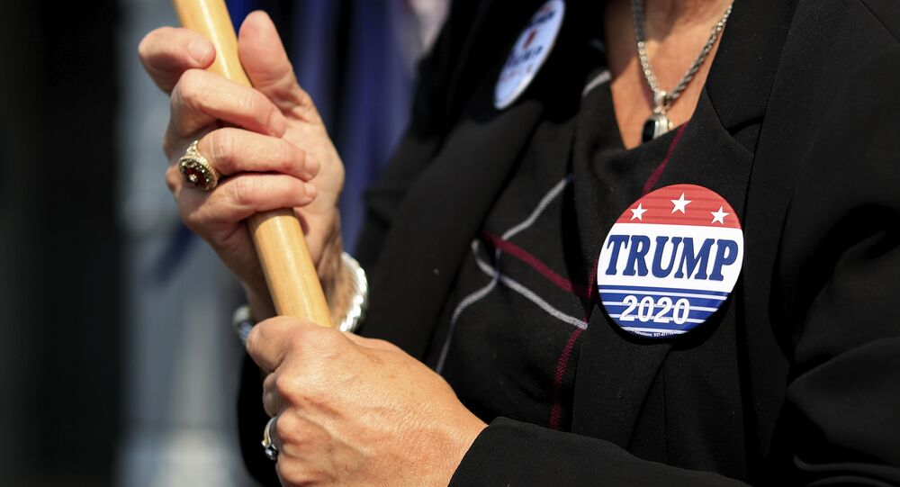 A view of a Trump button worn by a supporter, at the Hamilton County Board of Elections as people arrive to participate in early voting, Tuesday, Oct. 6, 2020, in Norwood, Ohio