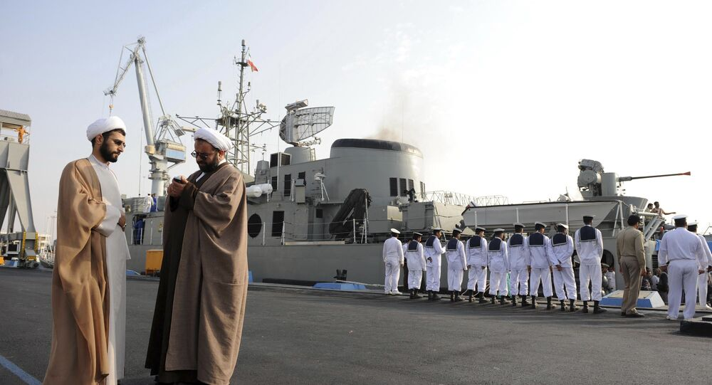 In this 21 February 2010 photo, two clerics stand to the left as Iran's Jamaran guided-missile destroyer and navy members prepare for an exercise in the Persian Gulf, along the coast of Iran.