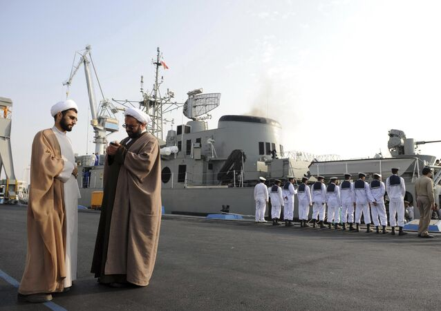 In this Feb. 21, 2010 photo, two clerics stand at left as Iran's Jamaran guided-missile destroyer and navy members prepare for an exercise in the Persian Gulf, along the coast of Iran.