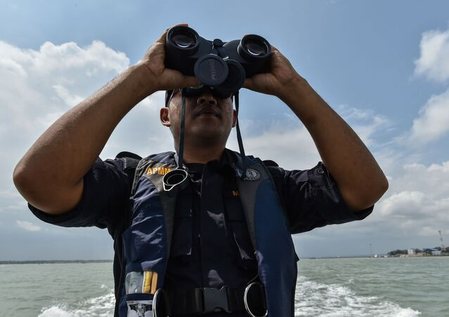 A member of the Malaysian Maritime Enforcement Agency officer uses a pair of binoculars to scan the sea during the rescue operation for the missing sailors from the USS John S. McCain off the Johor coast of Malaysia on August 24, 2017. - The US destroyer John S. McCain collided with a tanker early on August 21 as the warship prepared to make a routine port call in Singapore, leaving a gaping hole in its hull and 10 sailors missing.