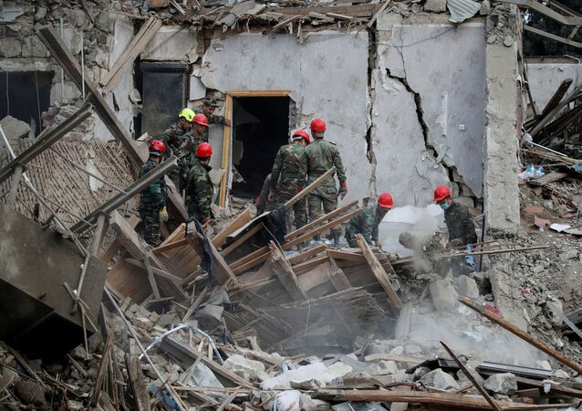Search and rescue teams work on the blast site hit by a rocket during the fighting over the breakaway region of Nagorno-Karabakh in the city of Ganja, Azerbaijan October 11, 2020.