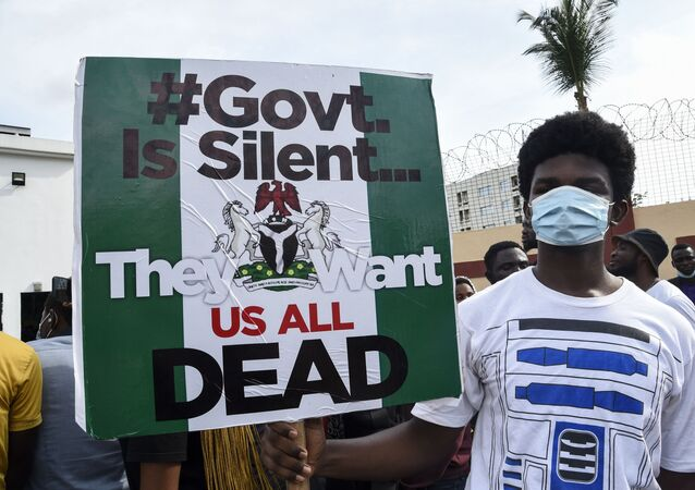 A young man holds a sign during a demonstration calling for the scrapping of the controversial Special Anti-Robbery Squad SARS police unit, in Ikeja, on October 8, 2020. - Nigeria's top police chief on October 4 banned a controversial anti-robbery unit and other special agents from mounting roadblocks and carrying out stop-and-search operations over accusations of abuses. Inspector-General of Police Muhammed Adamu said the Federal Special Anti-Robbery Squad (FSARS) and other tactical squads must stop such operations with immediate effect. Adamu said the decision followed findings that a few personnel in undercover tactical squads have abused their position to perpetrate all forms of illegality.