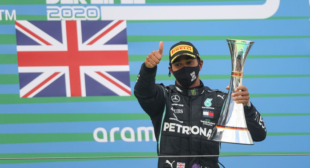 Winner Mercedes' British driver Lewis Hamilton celebrates winning with the trophy on the podium after the German Formula One Eifel Grand Prix at the Nuerburgring circuit in Nuerburg, western Germany, on October 11, 2020.