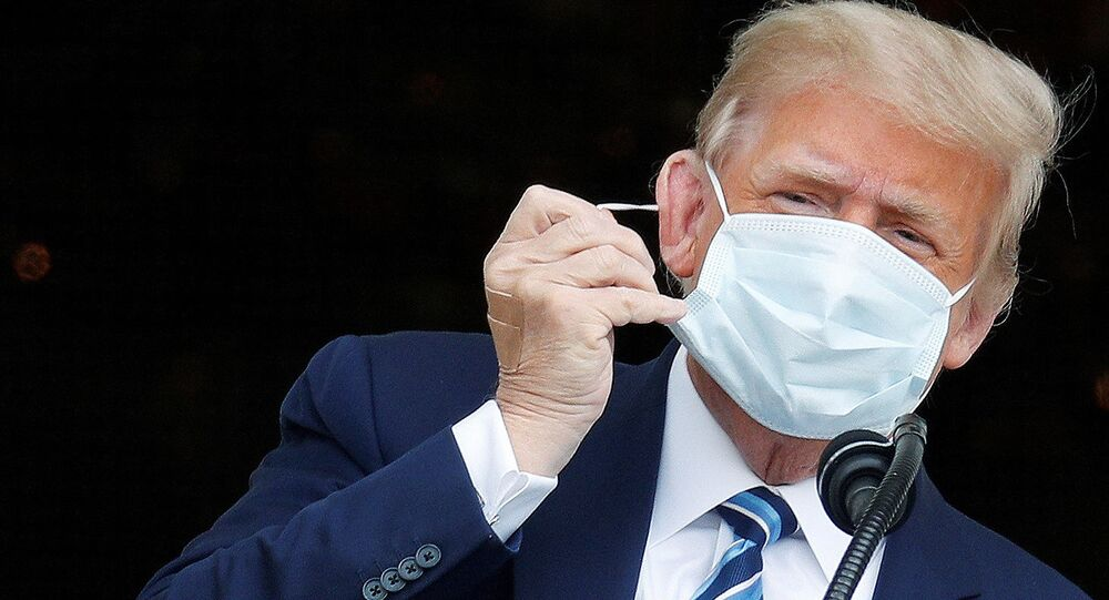 U.S. President Donald Trump, with bandages seen on his hand, takes off his face mask as he comes out on a White House balcony to speak to supporters gathered on the South Lawn for a campaign rally that the White House is calling a peaceful protest in Washington, U.S., October 10, 2020.