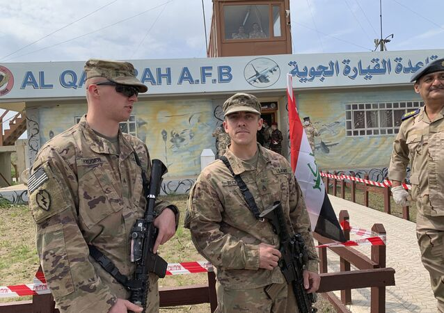 U.S. soldiers stand guard during the hand over ceremony of Qayyarah Airfield, Iraqi Security Forces, in the south of Mosul, Iraq  early Friday, March 27, 2020. Iraq's military on Thursday said at least two rockets hit inside Baghdad's heavily fortified Green Zone, the seat of Iraq's government and home to the American Embassy, in the first attack following a brief lull in violence from earlier this month.