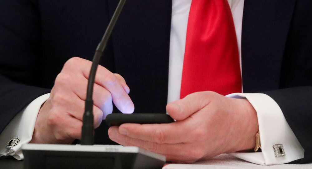 U.S. President Donald Trump taps the screen on a mobile phone at the approximate time a tweet was released from his Twitter account, during a roundtable discussion on the reopening of small businesses in the State Dining Room at the White House in Washington, U.S., June 18, 2020