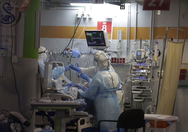 Medical professionals in full protective equipment tend to an elderly man on a ventilator in the critical care coronavirus unit, which was built in an underground parking garage at Sheba Medical center in Ramat Gan, Israel, Wednesday, Sept. 30, 2020, amid a spike in COVID-19 cases.