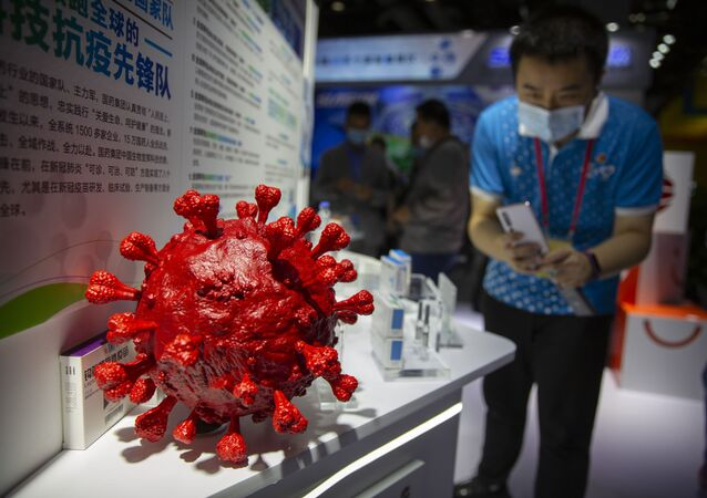 A visitor wearing a face mask takes a photo of a model of a coronavirus and boxes for COVID-19 vaccines at a display by Chinese pharmaceutical firm Sinopharm at the China International Fair for Trade in Services (CIFTIS) in Beijing, Saturday, Sept. 5, 2020. With the COVID-19 pandemic largely under control, China's capital on Saturday kicked off one of the first large-scale public events since the start of the coronavirus outbreak, as tens of thousands of attendees were expected to visit displays from nearly 2,000 Chinese and foreign companies showcasing their products and services.