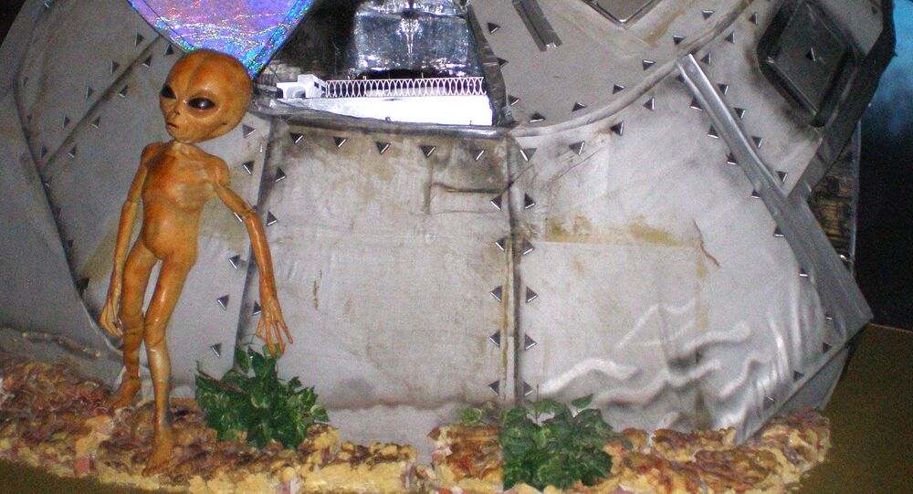 This photo taken in December 2006 at the Area 51 exhibit at the Alien Zone in Roswell, N.M., shows a model alien standing outside a crashed spaceship.