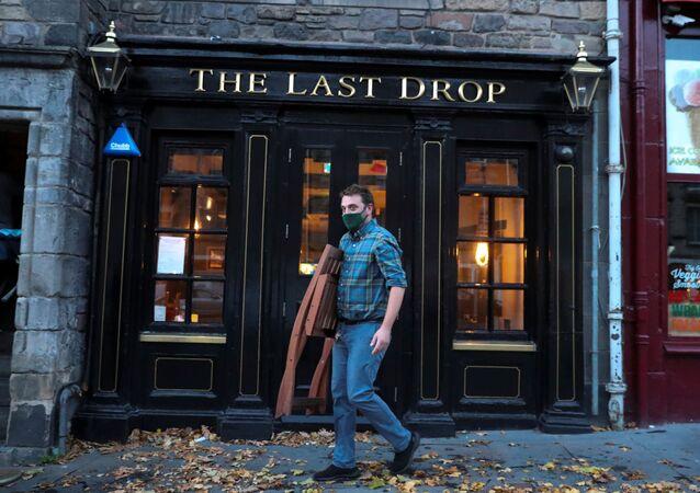 A worker carries a chair as he prepares to close a pub at Grassmarket, amid the coronavirus disease (COVID-19) outbreak, in Edinburgh, Britain October 9, 2020.