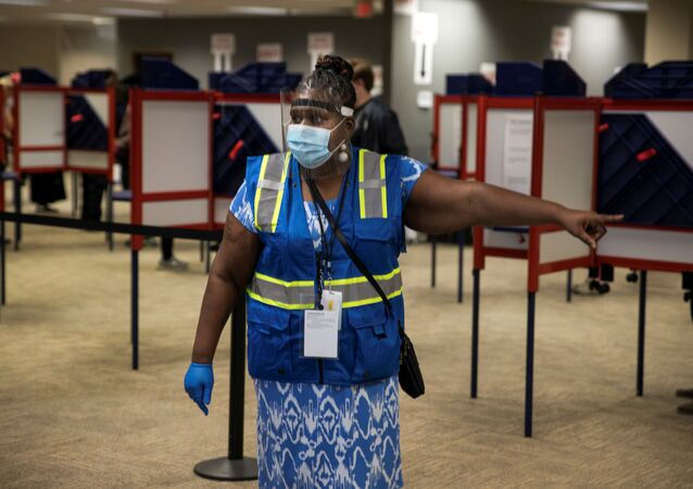 A poll worker directs voters to cast their ballots for the upcoming presidential election as early voting begins in Cincinnati, Ohio, U.S., October 6, 2020