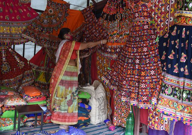 A vendor wearing a facemask as a protection against the Covid-19 Coronavirus, arranges traditional dresses ahead of the forthcoming Hindu festival 'Navratri', a nine-night dance festival, at Law Garden Bazaar in Ahmedabad on September 21, 2020.