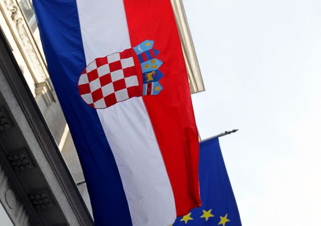 A state flag of Croatia and a European Union flag on a building in Zagreb.