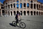 A man wearing a protective face mask cycles past the Colosseum as local authorities in the Italian capital Rome ordered face coverings to be worn at all times outdoors, in an effort to counter the spread of the coronavirus disease (COVID-19), in Rome, Italy, October 8, 2020.