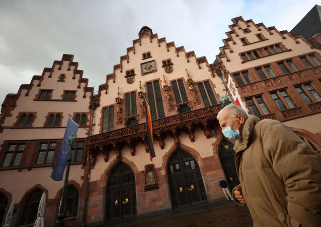 A man wearing a face mask walks in front of the Roemer townhall, as the spread of the coronavirus disease (COVID-19) continues, in Frankfurt, Germany, October 12, 2020.