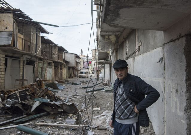 A man stands near a house with a row of destroyed barns in the background in Stepanakert, a self-proclaimed Republic of the Nagorno-Karabakh.