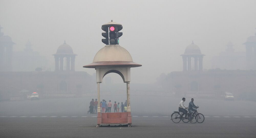 Cyclist pedal through the morning smog a day after Diwali festival, in New Delhi, India, Friday, Oct. 20, 2017