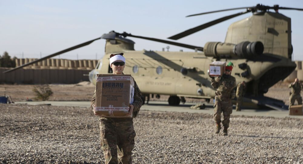 In this Tuesday, Dec. 24, 2019, photo, U.S. service members deliver Christmas gifts to their comrades on a base near the al-Omar oilfield in eastern Syria.