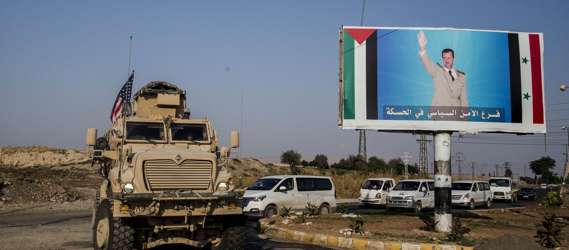 FILE - In this Saturday, 26 October 2019 file photo, a US military vehicle drives south of the northeastern city of Qamishli, likely heading to the oil-rich Deir el-Zour area where there are oil fields, or possibly to another base nearby, as it passes by a poster showing Syrian President Bashar Assad. - Sputnik International, 1920, 13.10.2020