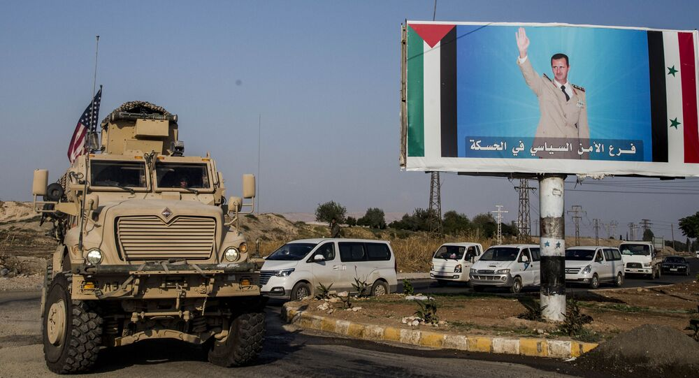 FILE - In this Saturday, 26 October 2019 file photo, a US military vehicle drives south of the northeastern city of Qamishli, likely heading to the oil-rich Deir el-Zour area where there are oil fields, or possibly to another base nearby, as it passes by a poster showing Syrian President Bashar Assad.