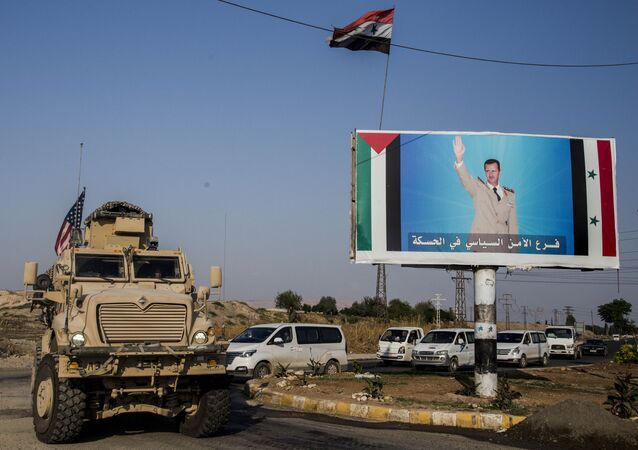 FILE - In this Saturday, Oct. 26. 2019 file photo, a U.S. military vehicle drives south of the northeastern city of Qamishli, likely heading to the oil-rich Deir el-Zour area where there are oil fields, or possibly to another base nearby, as it passes by a poster showing Syrain President Bashar Assad.