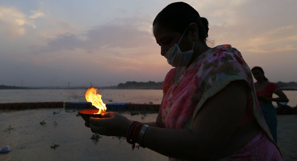 A Hindu devotee offers evening prayers in the River Ganges, during the Ganga Dussehra festival, in Prayagraj, India, Monday, June 1, 2020
