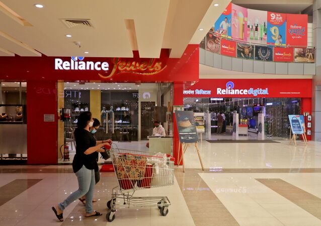 A customer wearing a protective mask pushes a trolley with grocery items past Reliance Jewels and Reliance Digital stores in Mumbai, India.