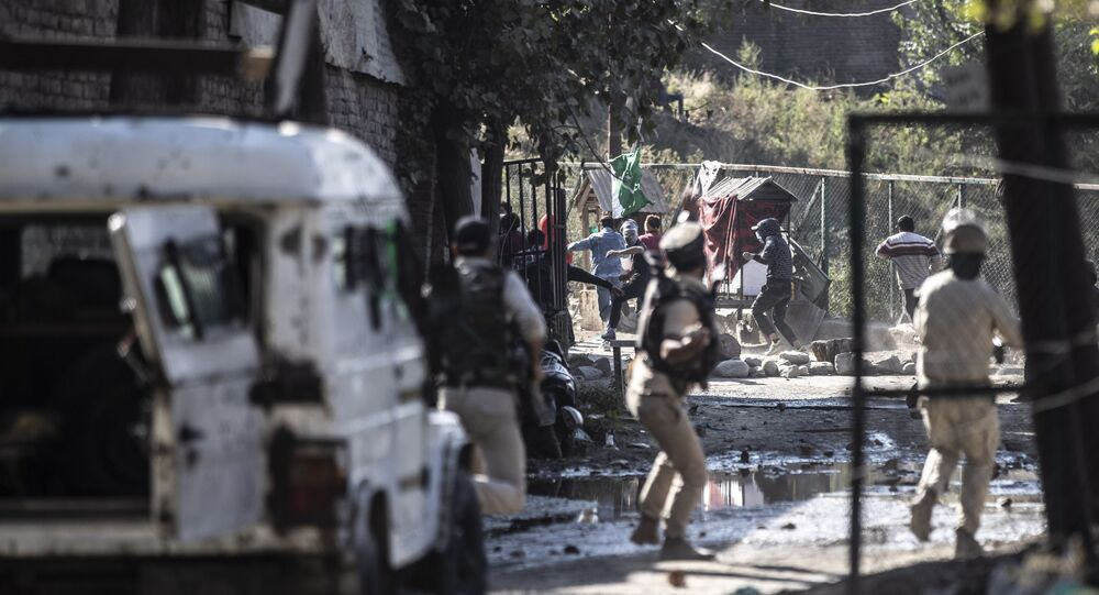 Indian policemen chase Kashmiri protesters during clashes following the killing of two suspected rebels in a gunfight with government forces in Srinagar, Indian controlled Kashmir, Monday, Oct. 12, 2020