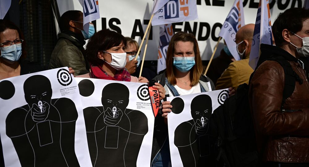 French police officers wearing face masks hold training targets as they gather in front of the police station of Champigny-sur-Marne, outside Paris, on October 12, 2020, to protest against their working conditions.