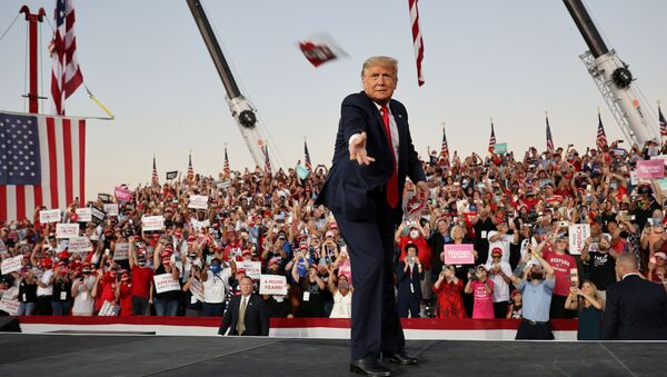 U.S. President Donald Trump tosses face masks to the crowd as he takes the stage for a campaign rally, his first since being treated for the coronavirus disease (COVID-19), at Orlando Sanford International Airport in Sanford, Florida, U.S., October 12, 2020. - Sputnik International