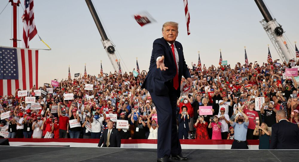 U.S. President Donald Trump tosses face masks to the crowd as he takes the stage for a campaign rally, his first since being treated for the coronavirus disease (COVID-19), at Orlando Sanford International Airport in Sanford, Florida, U.S., October 12, 2020.