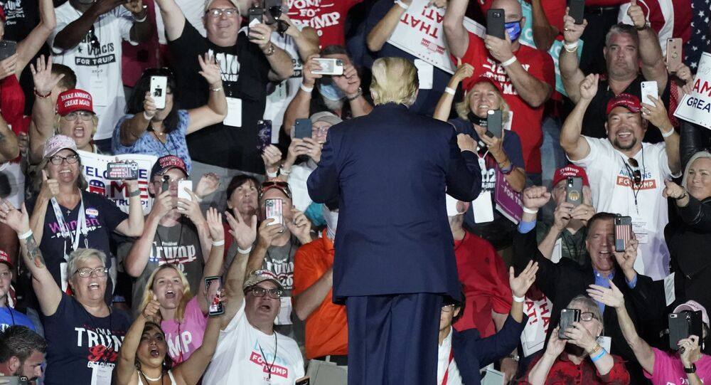 Supporters cheer as President Donald Trump leaves a campaign rally at Orlando Sanford International Airport Monday, 12 October 2020, in Sanford, Florida.