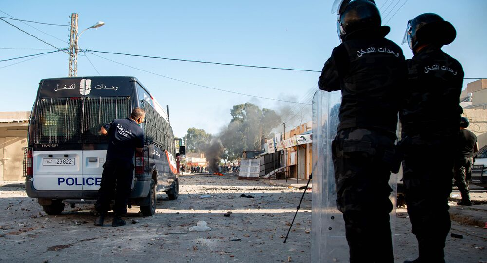 Tunisian security forces stand guard as protesters take to the streets of the impoverished Tunisian town of Sbeitla on October 13, 2020 after a man died when authorities demolished an illegal kiosk where he was sleeping.