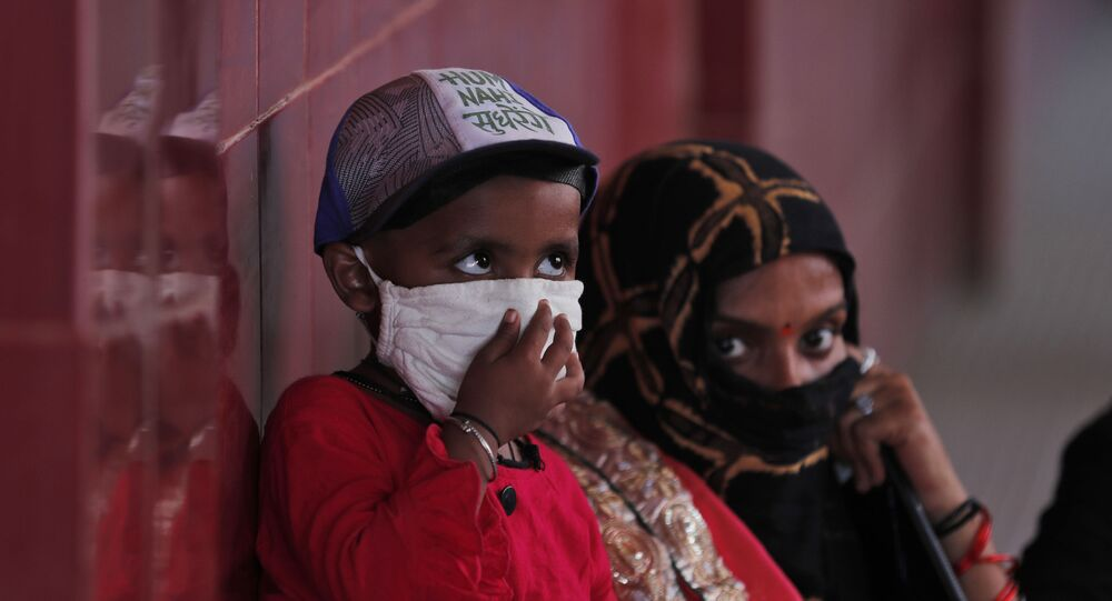 A woman and a child wait to give their nasal swab samples to test for COVID-19 at a government hospital in Unchahar, Raebareli district, Uttar Pradesh, India, Monday, Sept. 28, 2020.