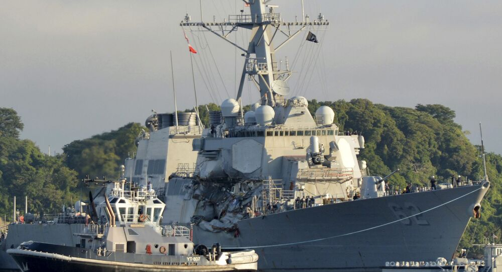 In this July 11, 2017 photo provided by U.S. Navy Office of Information, the Valiant-class yard tugboat Menominee (YT 807) assists the Arleigh Burke-class guided-missile destroyer USS Fitzgerald (DDG 62) as it moves to Dry Dock 4 at Fleet Activities (FLEACT) Yokosuka, Japan, to continue repairs and assess damage sustained from its June 17 collision with a merchant vessel.