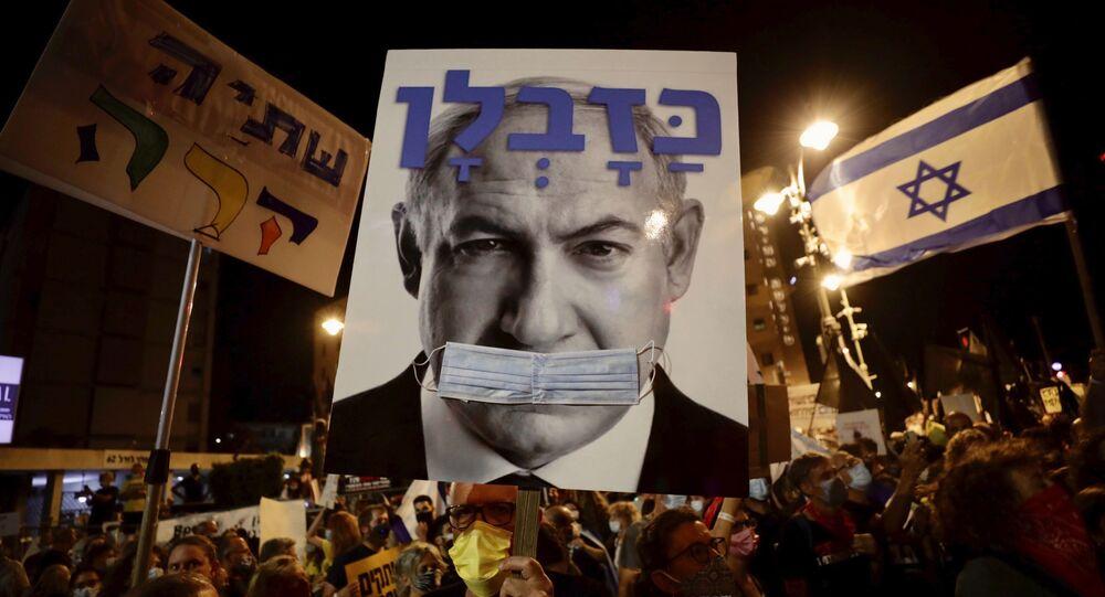 Israeli protesters hold signs during a demonstration against Israeli Prime Minister Benjamin Netanyahu outside the Prime Minister's residence in Jerusalem, Saturday, Sept. 12, 2020.