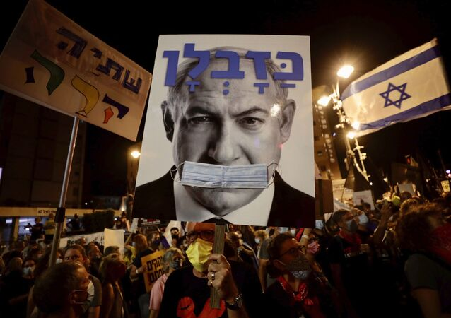 Israeli protesters hold signs during a demonstration against Israeli Prime Minister Benjamin Netanyahu outside the Prime Minister's residence in Jerusalem, Saturday, Sept. 12, 2020.