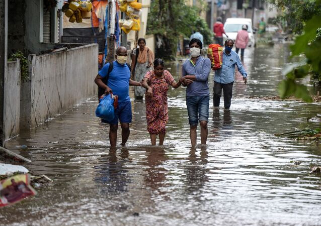 Residents carrying their belongings help a woman (C) while making their way on a flooded street following heavy rains in Hyderabad on October 14, 2020.
